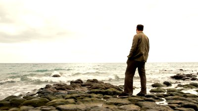 stock-footage-alone-man-standing-on-the-seashore