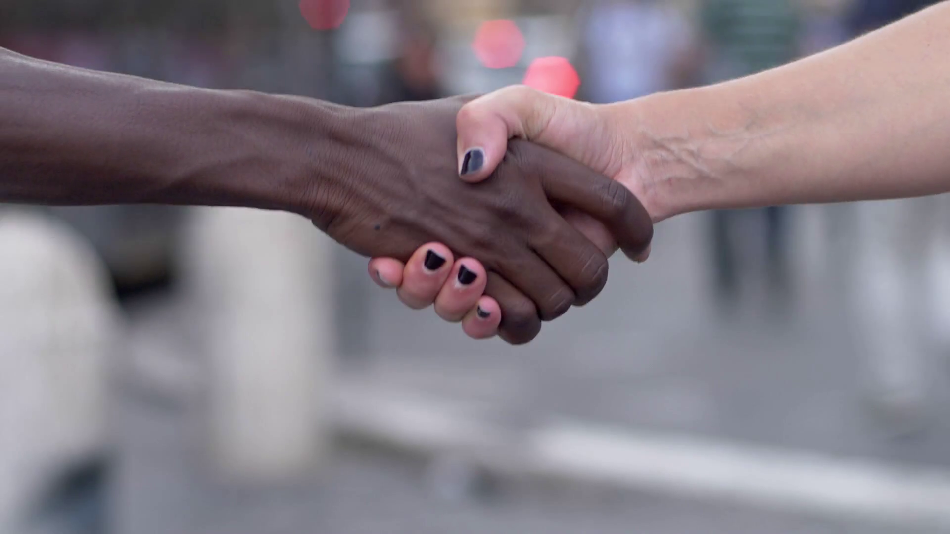 videoblocks-handshake-between-hand-of-black-man-and-white-woman-outdoor_rlphtvgo4m_thumbnail-full08